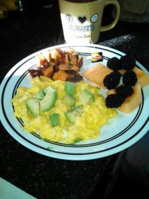 scrambled eggs topped with avocado, cantaloupe and blackberries, roasted sweets
